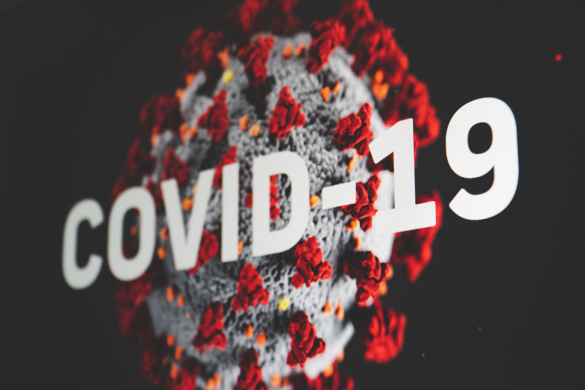"""A Covid-19 virus with the text, """"Covid-19"""" overlaid on top."""