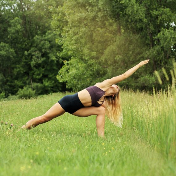 A woman does yoga outside in a green field.