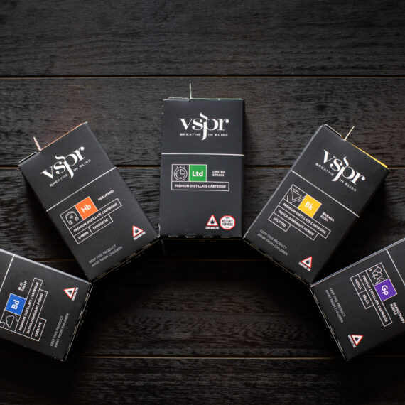 A collection of VSPR vape cartridges against a dark wood background.
