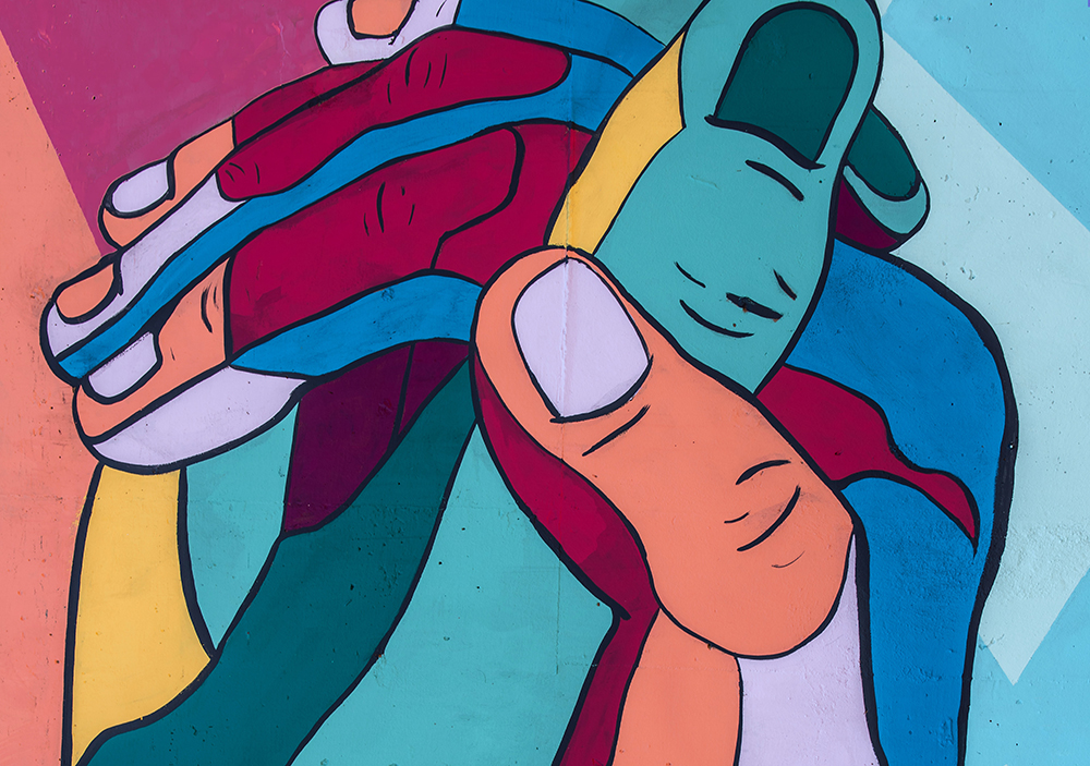 A mural of colorful, clasping hands.