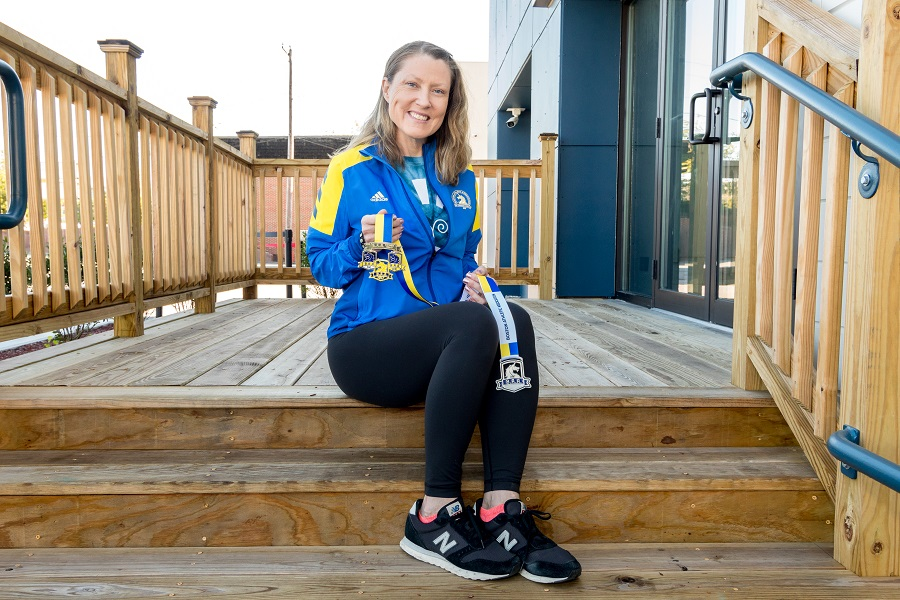 Heather Ryan seen sitting on the steps in front of Framingham store holding her medals.