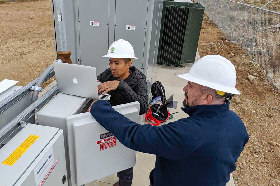 two workers with a computer at a substation