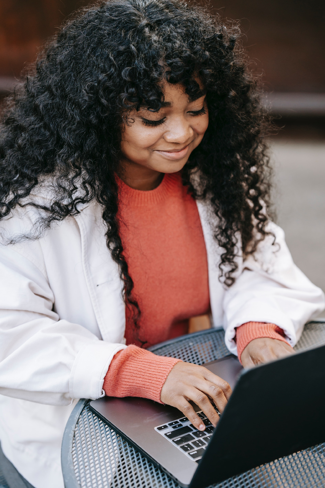 Lady smiling while typing on her laptop