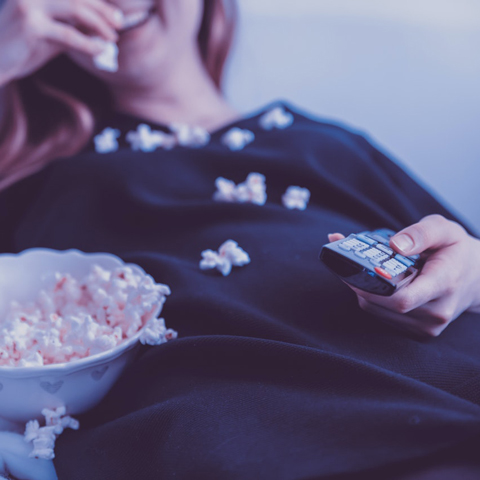 Lady watching a movie and eating popcorn