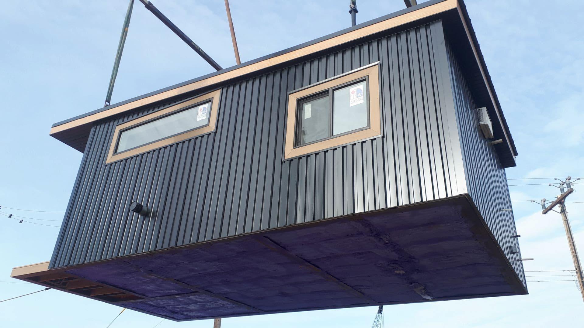 Modular shipping container home with black and wooden accents