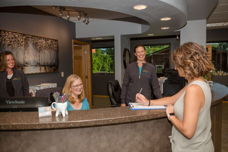 front desk staff checking in a patient