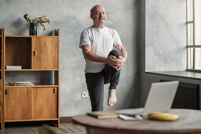 Senior exercising at home in front of computer using telehealth