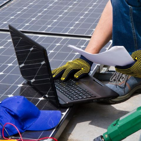 Person on laptop outside next to solar panels.
