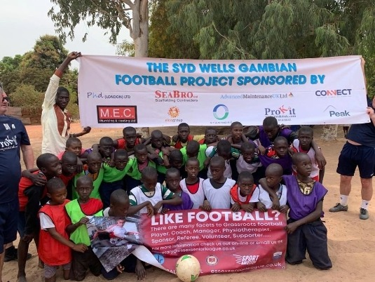 Gambian children huddled below a 'The Syd Wells Gambian Football Project' banner.