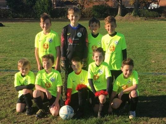 Children in football team posing for team photo.