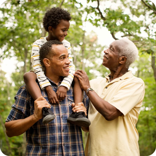 A son sitting on his father's shoulders, both greeted by an elderly man