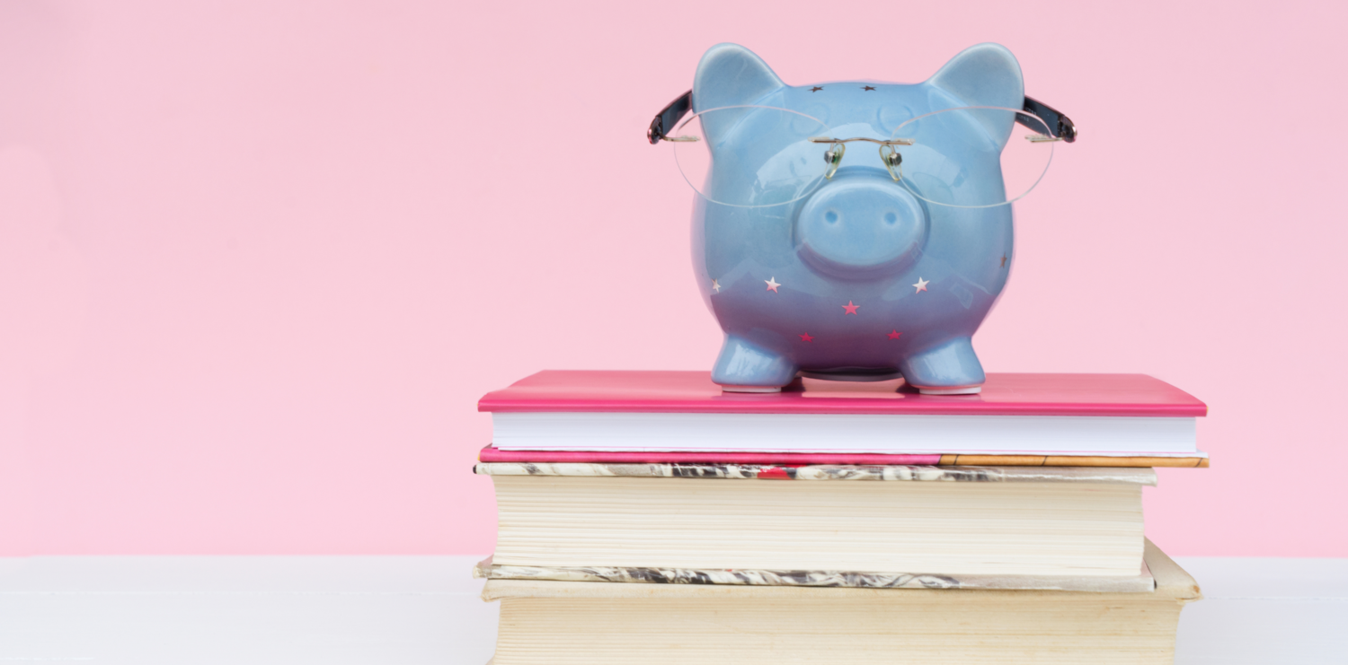 A piggy bank sat on top of some books set against a pink background