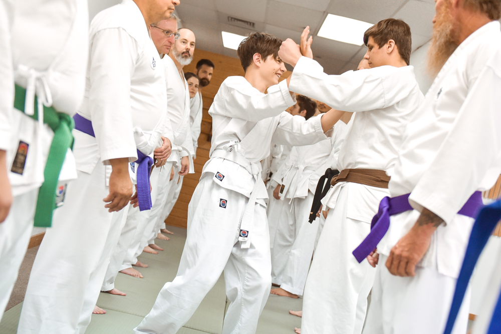 An NGA White Belt is seen participating and practicing their two-hand blocks during the Gauntlet Line session.