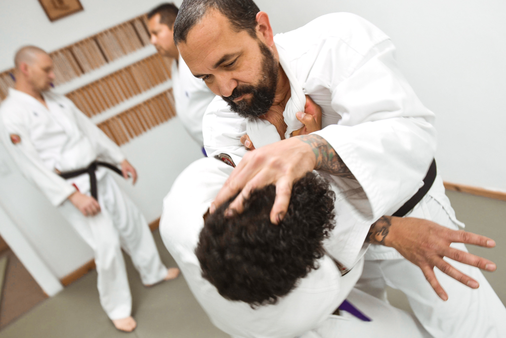 An NGA Black Belt instructor is seen controlling his partner (uke) from a two-handed grip to his collar.
