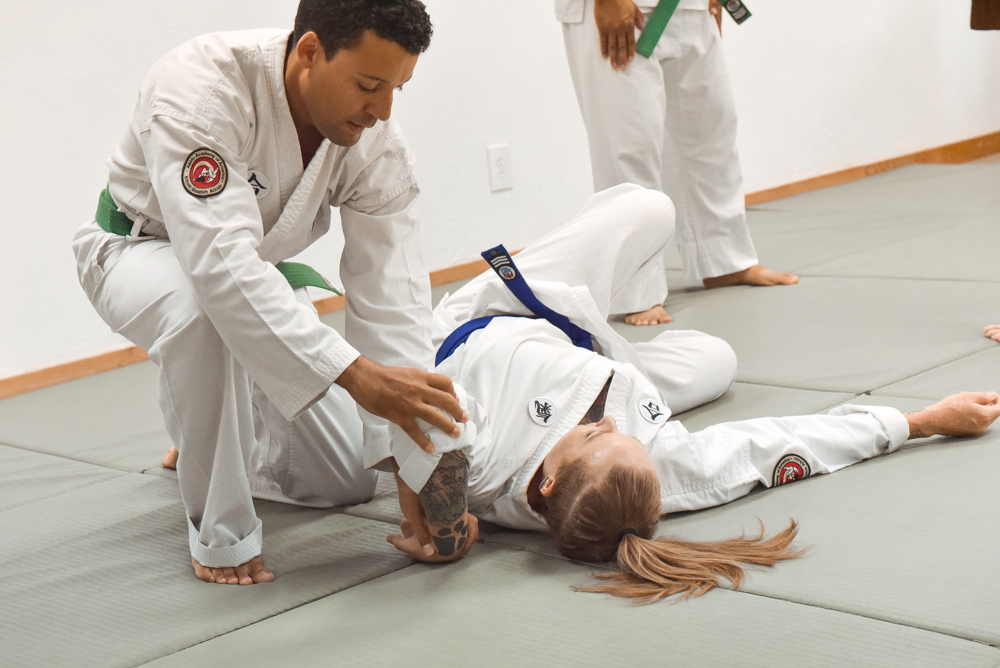 An NGA Green Belt performs a Pivot Takedown Hold Down classical technique on a Blue Belt student.
