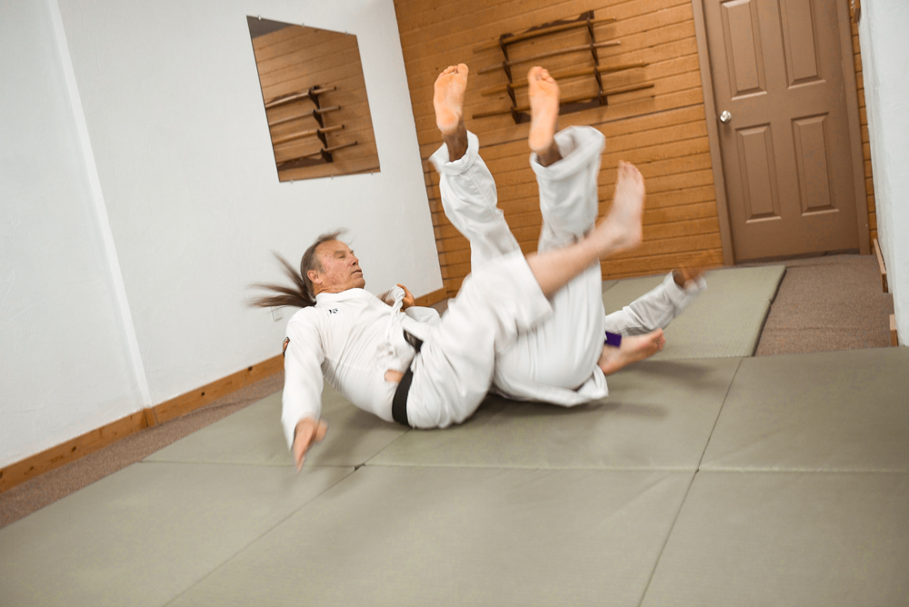 An NGA Black Belt is seen teaching the Scissors classical technique, which requires the instructor to launch themselves towards their partner (uke) using their legs to scissor and twist their partner's back toward the ground.