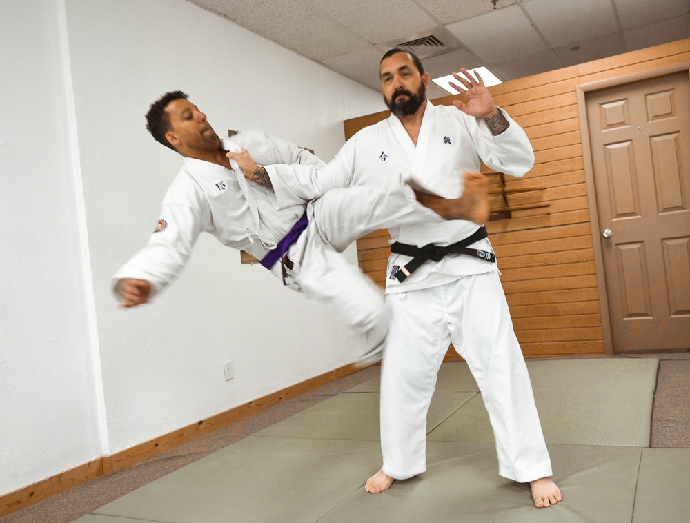 An NGA Purple Belt is seen practicing the Scissors classical technique on their partner (uke).