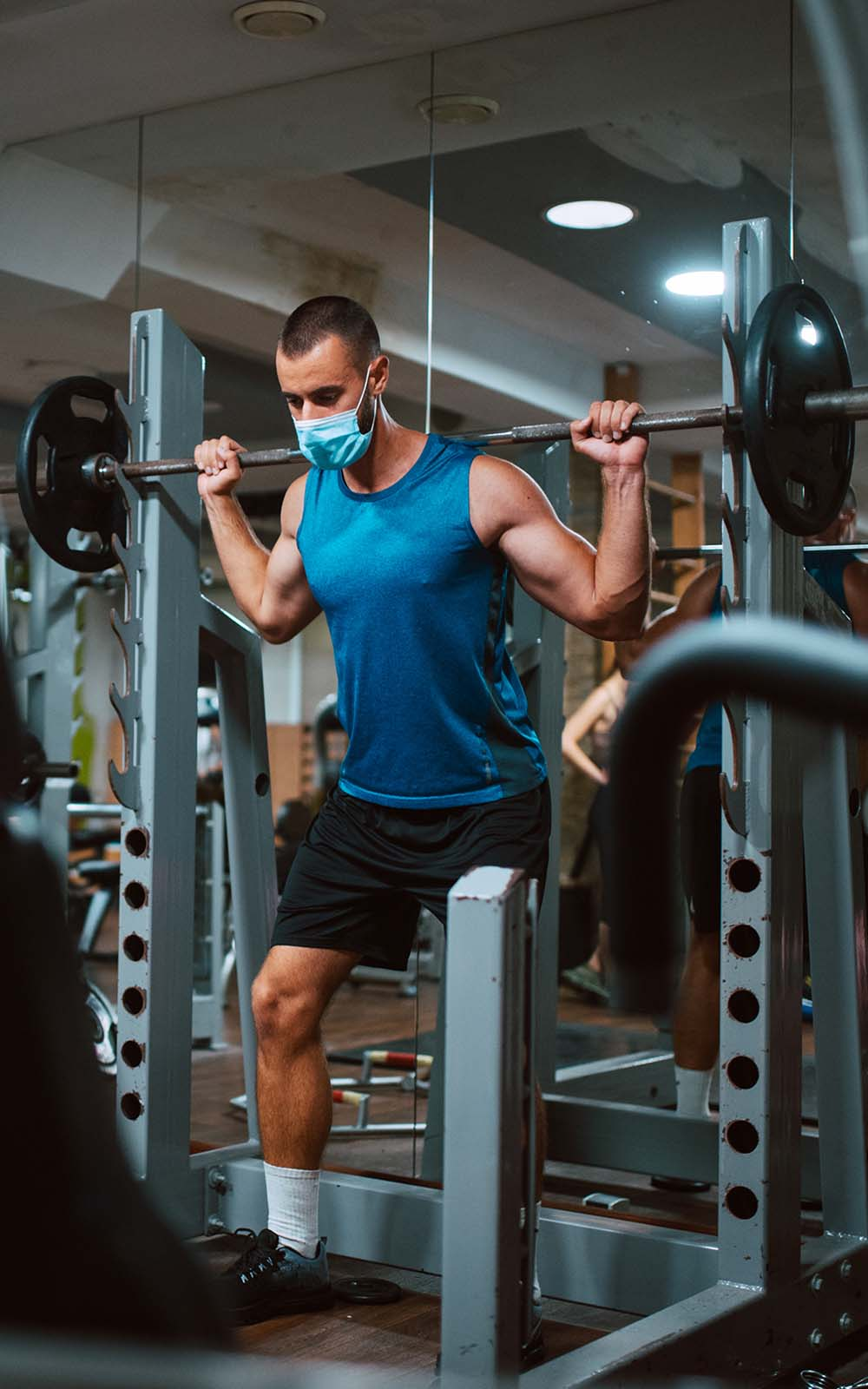 Masked male lifting weights