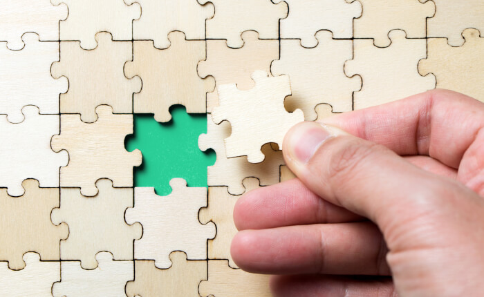The last piece of a jigsaw wooden puzzle and how PensionSync helps people to solve problems.