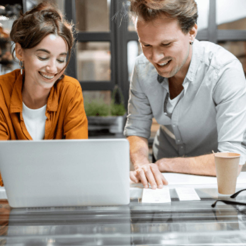 Office workers having a conversation in front of laptop