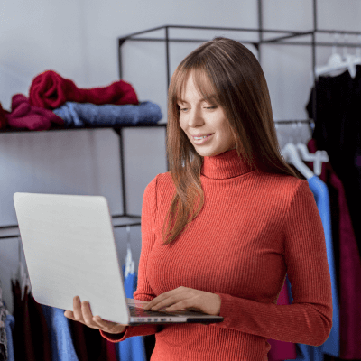 Woman working in retail shop with laptop