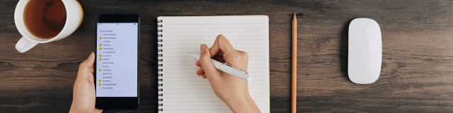 Person writing a checklist on notebook