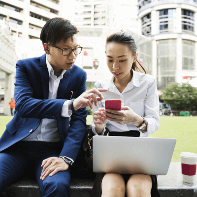Office workers sitting together on laptop and phone on the grass outside the office