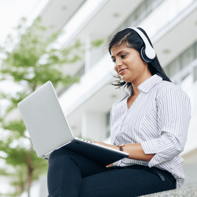 Woman on laptop working with headphones
