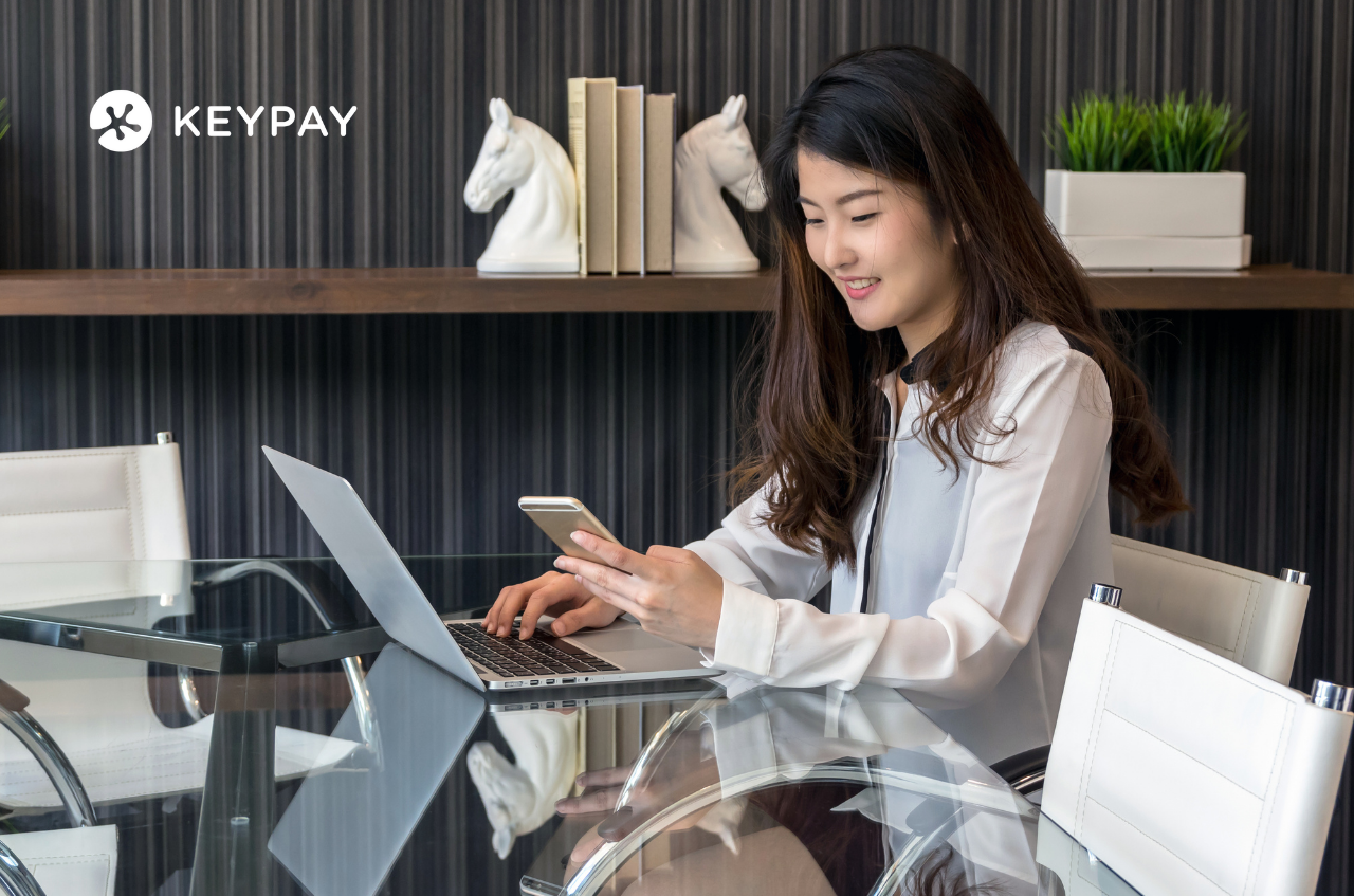 KeyPay's Document Acknowledgement Report. Office worker sitting at the desk and looking at her laptop and holding her mobile phone on her left hand.