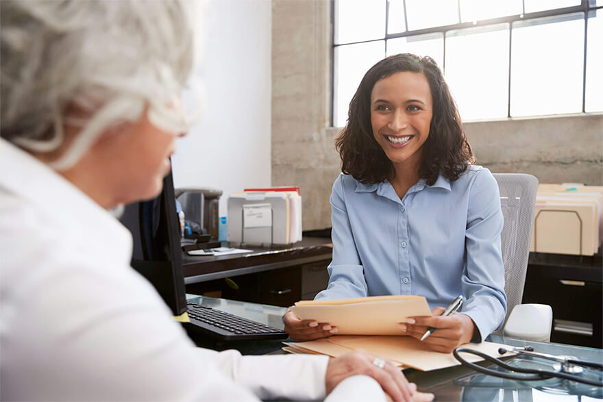 An advisor holding folders while sitting at her desk and speaking to an elderly woman.