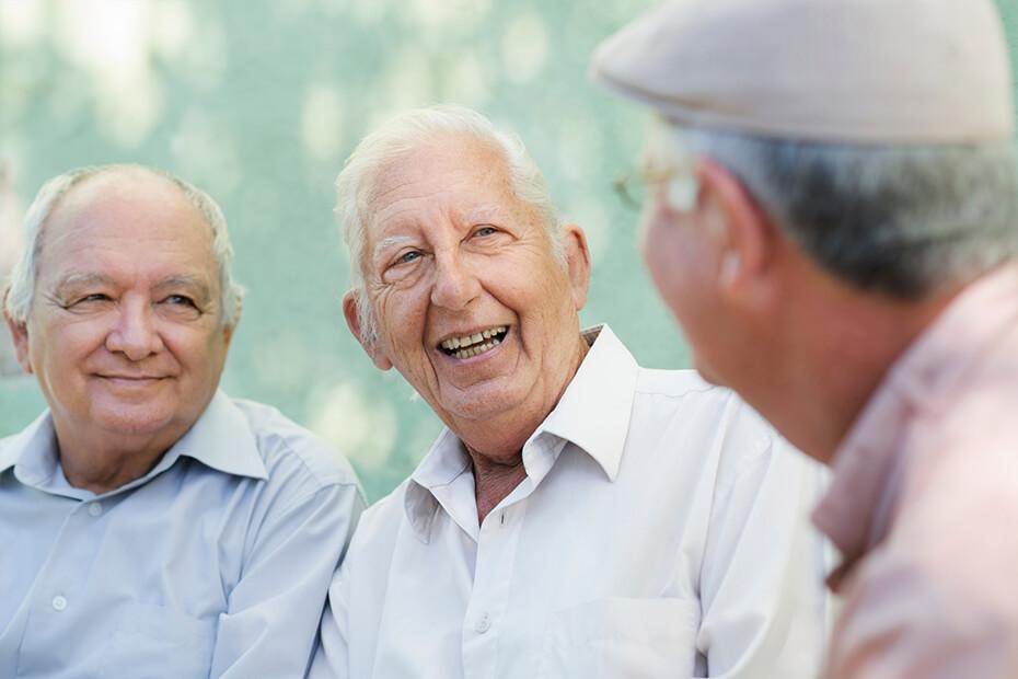 Three elderly man conversing.