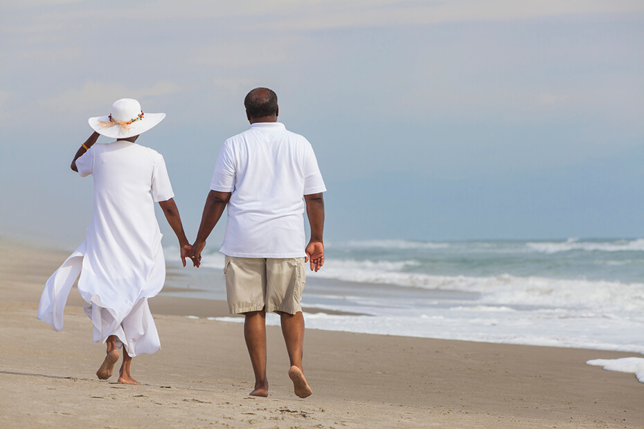An elderly man and woman holding hands and walking on the beach with their backs facing the camera.