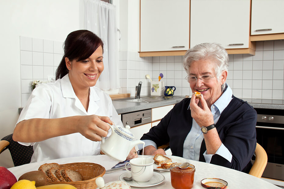 A caretaker pouring a beverage in an elderly woman's mug. There is breakfast all around the table.