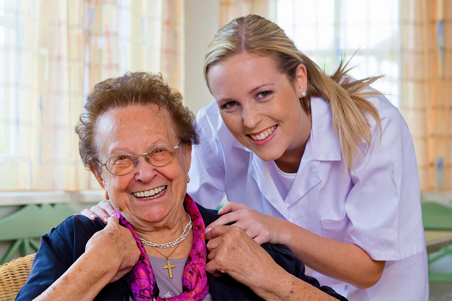 An elderly woman and her caretaker smiling.