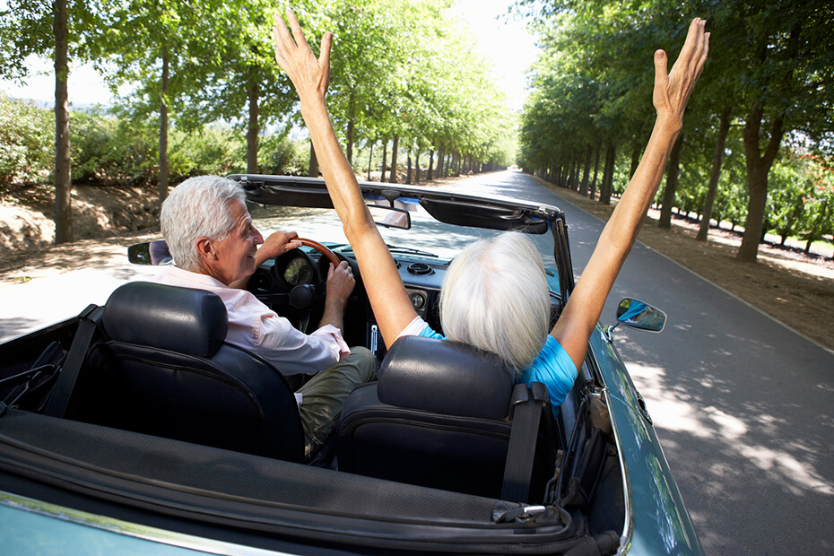 An elderly man driving a blue car with an elderly lady in the passenger seat with her hands in the air,