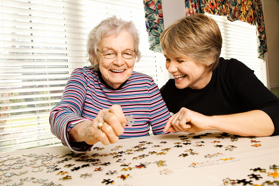 Two elderly women smiling and putting together a jigsaw puzzle.