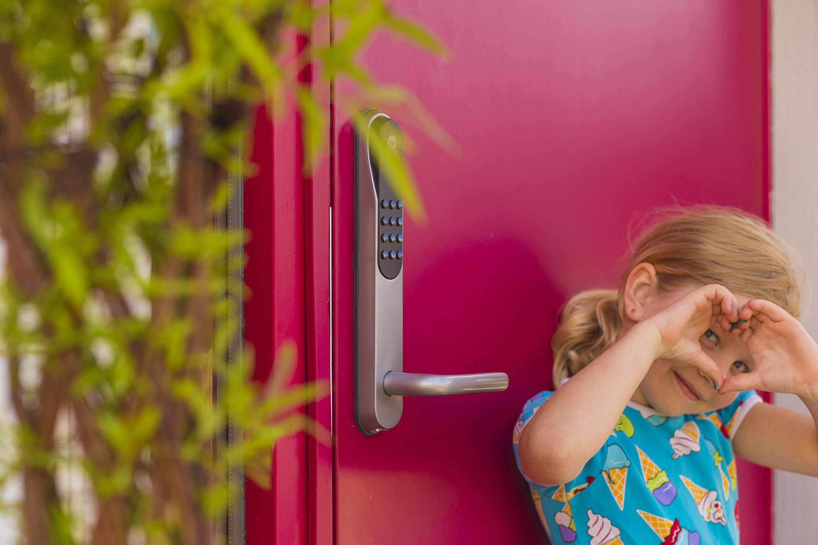 Flicka ståendes framför röd dörr.