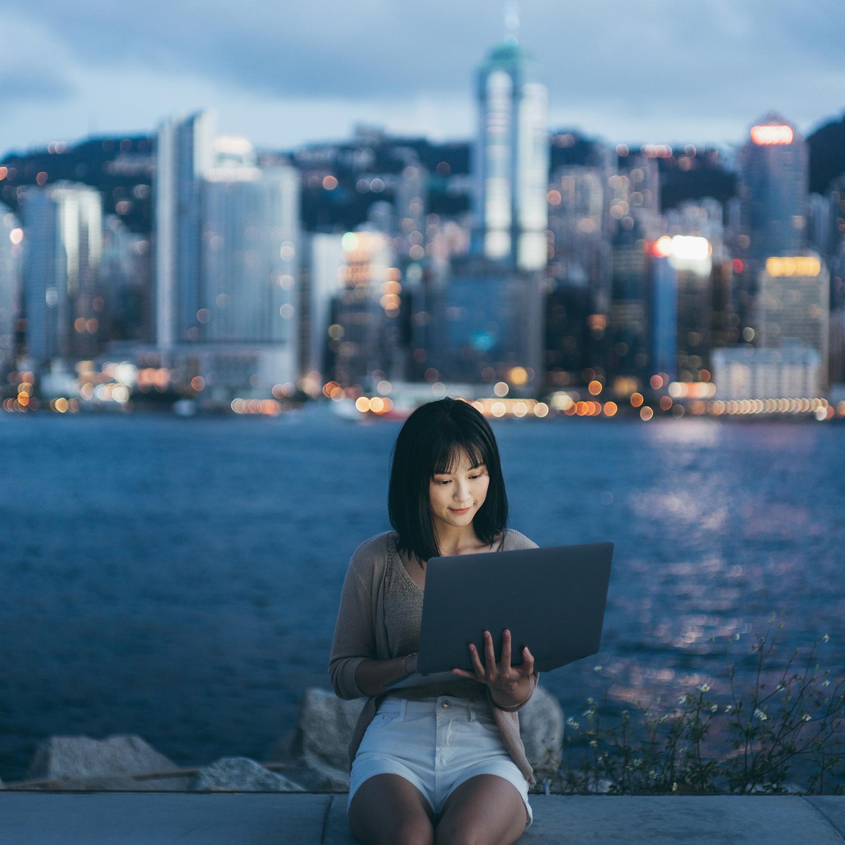 Kvinna som sitter med lap-top på en pir.