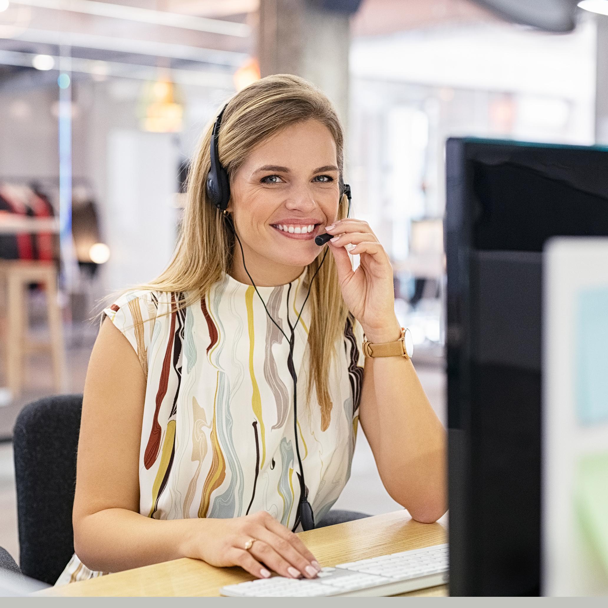 Person i kundsupport som svarar i telefon framför datorskärm.