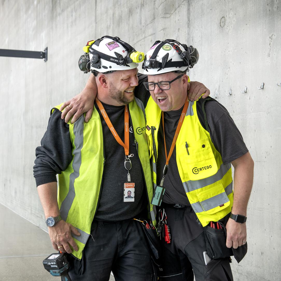 Två män i signalvästar som har roligt på arbetet.