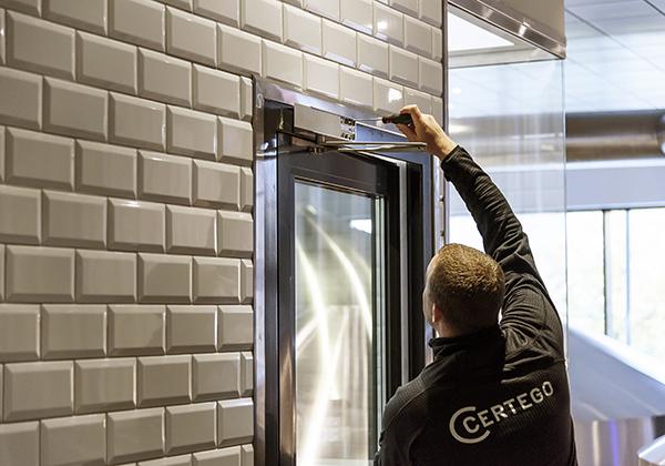 Servicetekniker som skruvar på en dörrstängare.