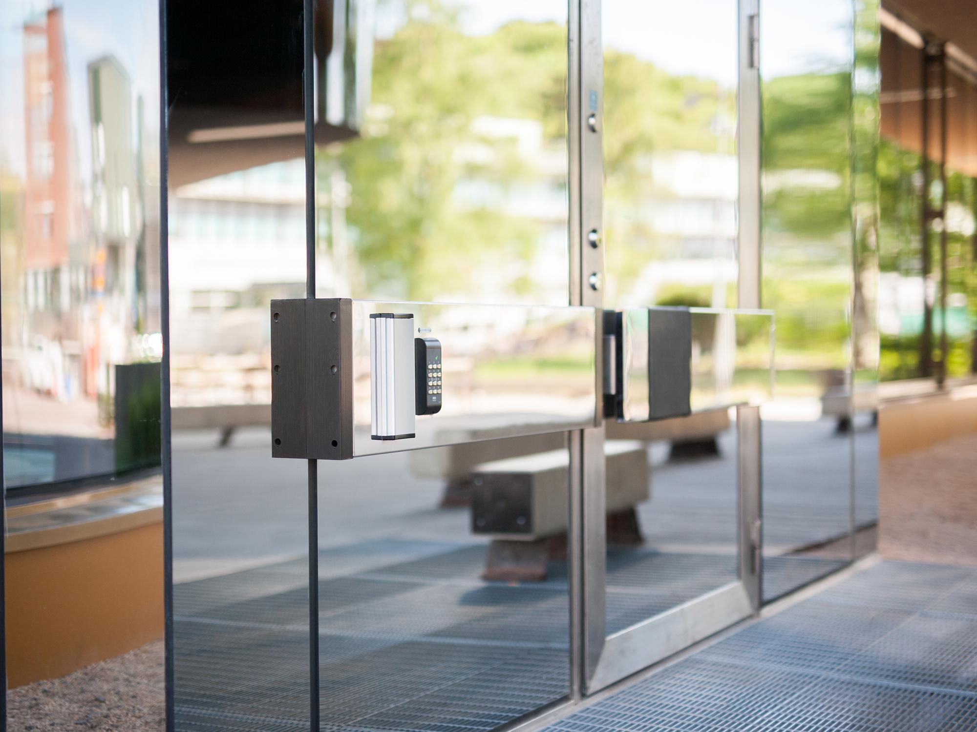 Entrédörr med passersystem i glaspartier i fasad.