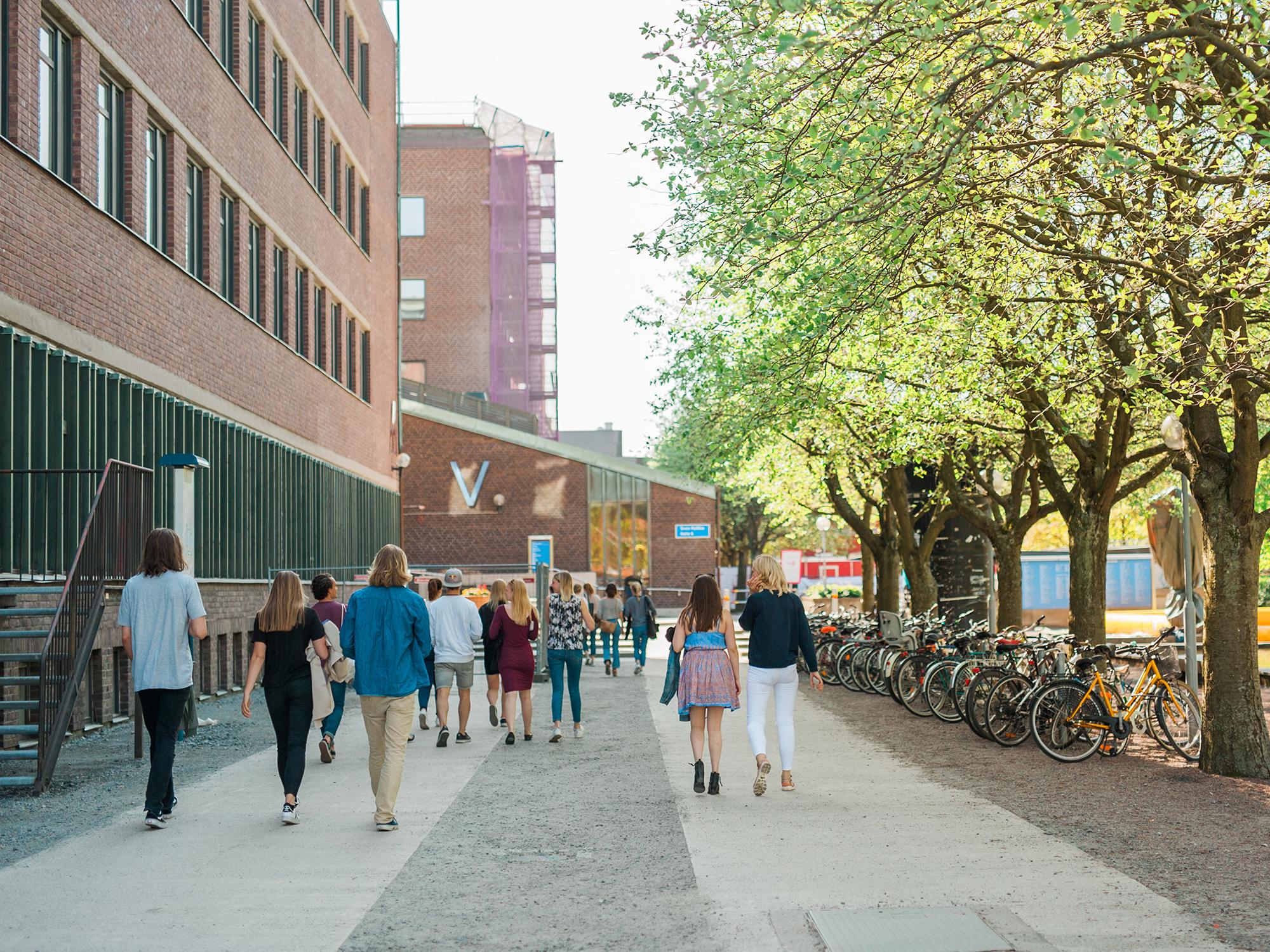 Sommarklädda studenter som går utanför campus på ett universitet.