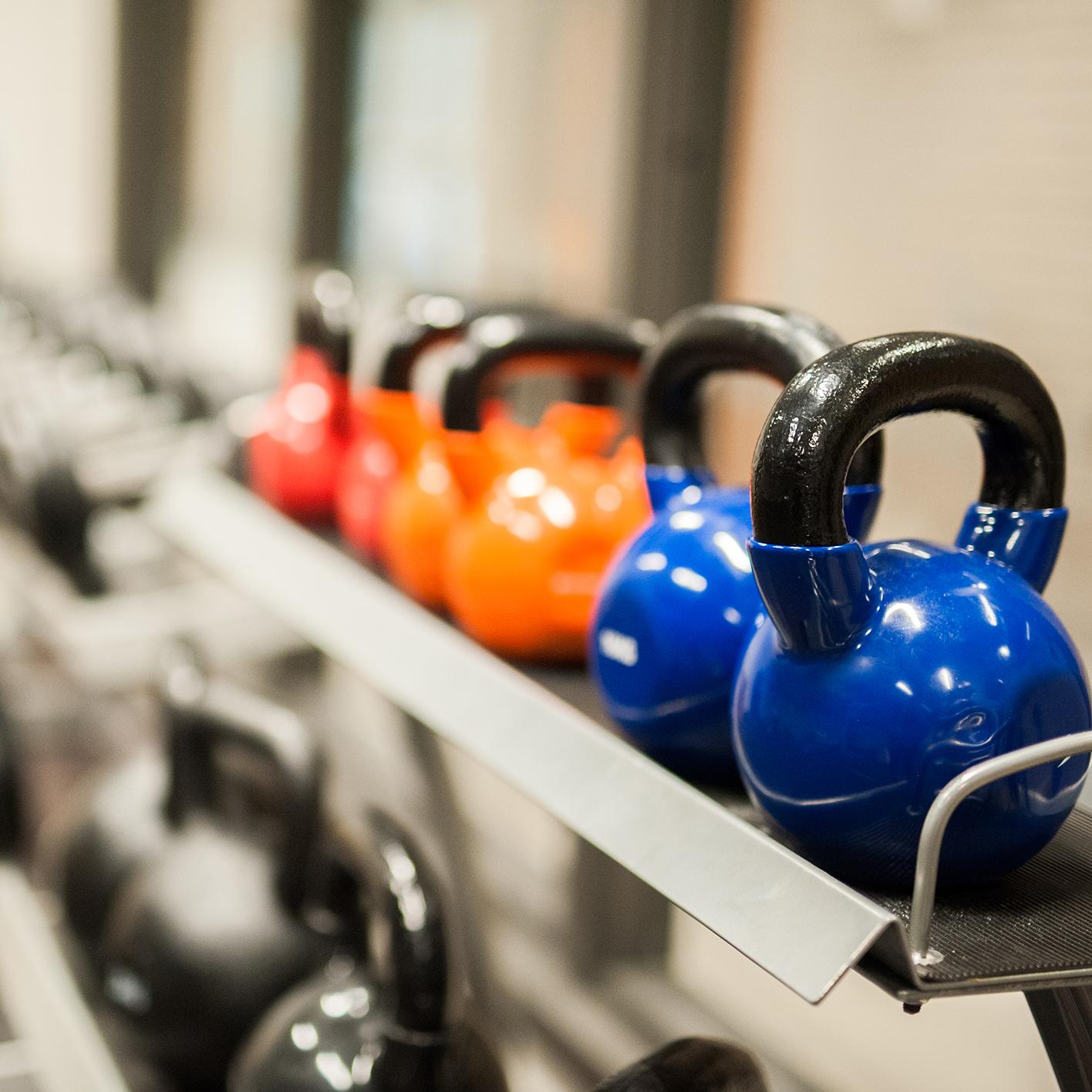 Ett ställ med färglada kettelbells på ett gym.