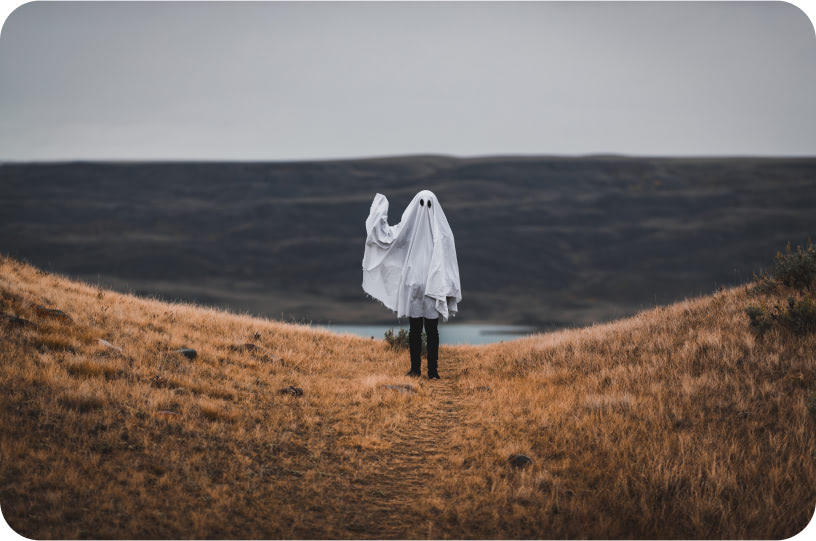 Person in ghost costume waving hello