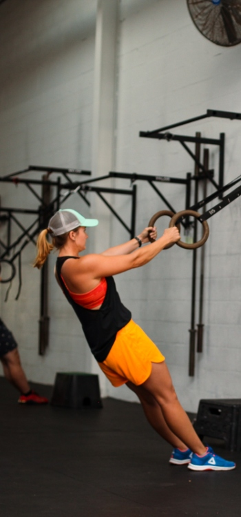 A man and a woman doing ring rows