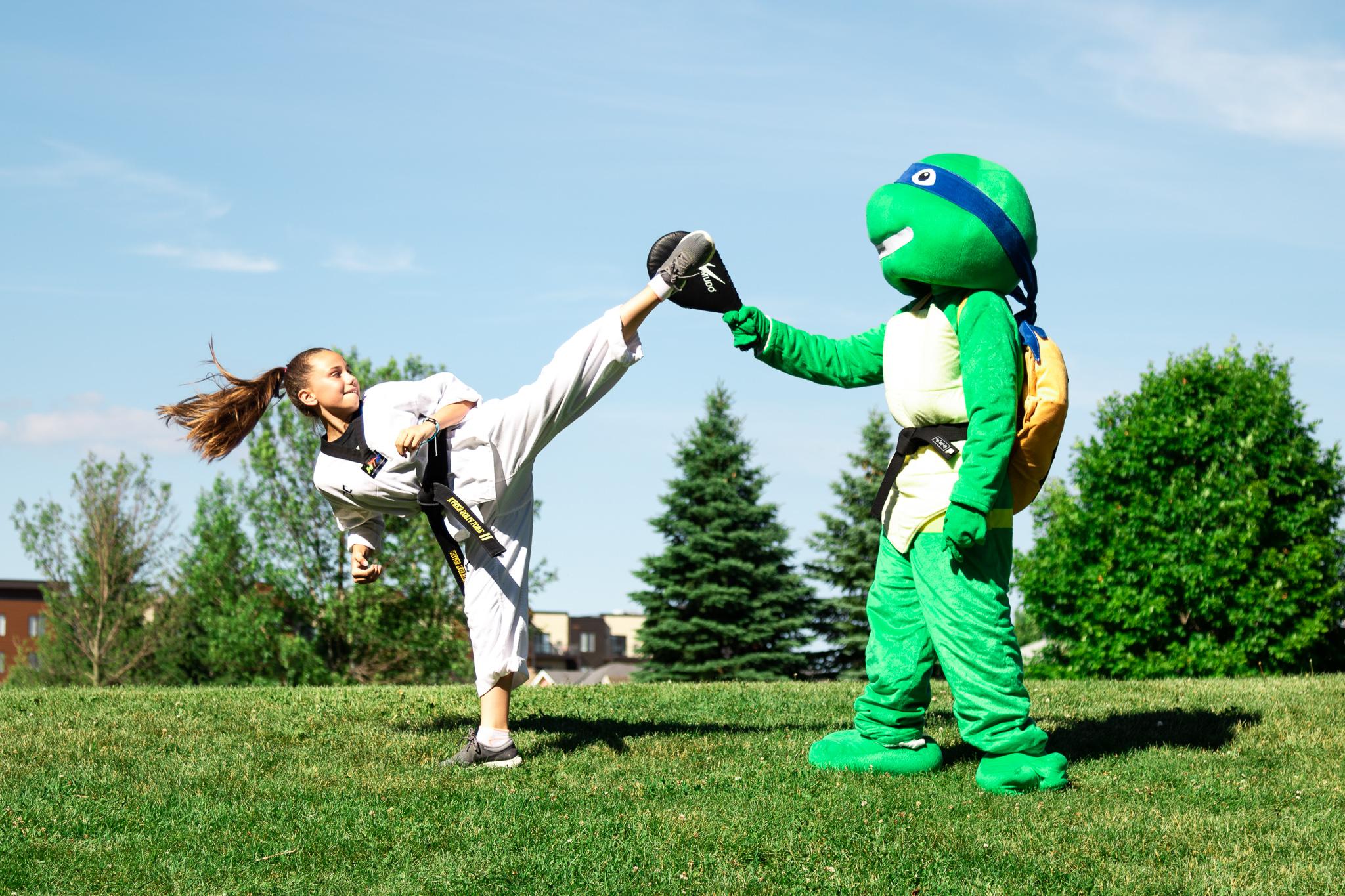 A girl kicking a target held by a teenage mutant ninja turtle