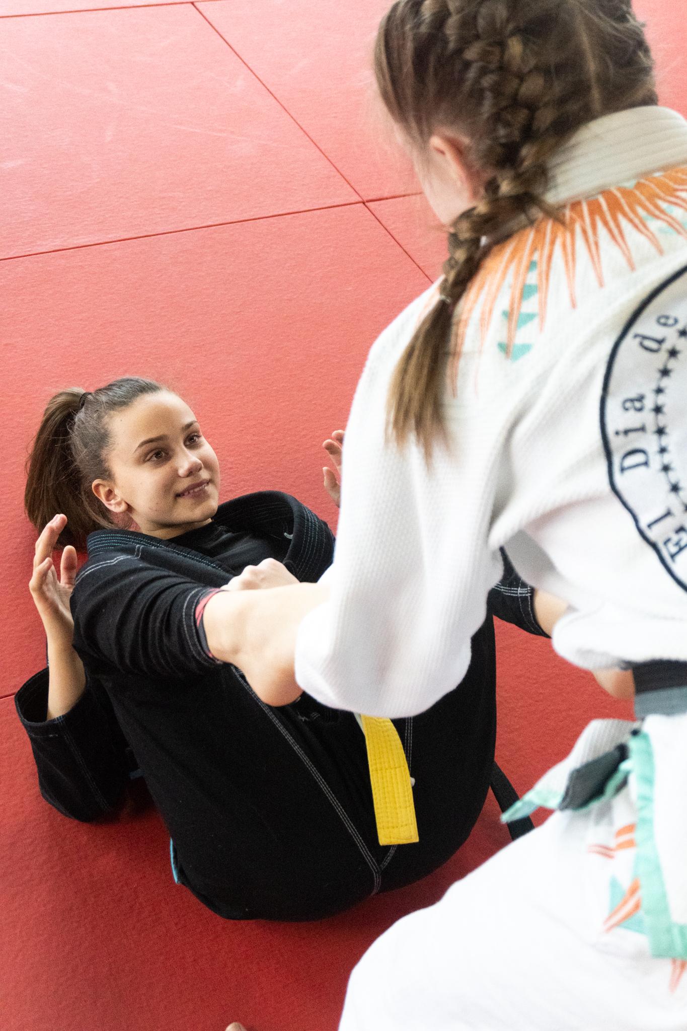 A teenage girl having fun training Brazilian jiu-jitsu