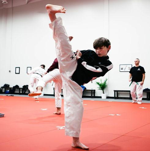 A teenager performing a turning kick