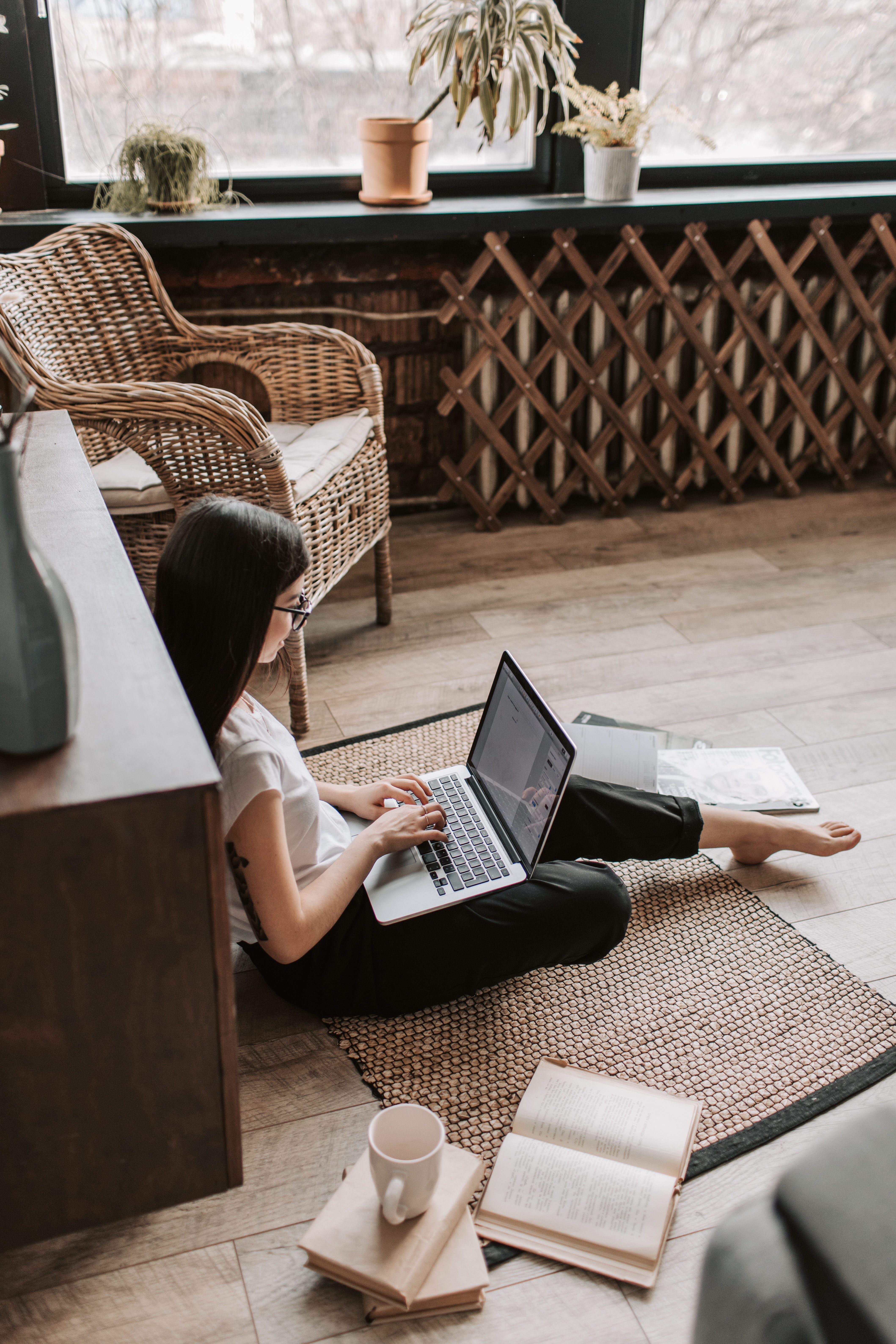 A young woman sitting on the floor and working on her laptop.